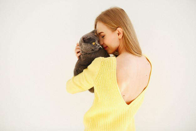 lady-in-yellow-dress-with-open-back-holds-grey-cat-on-her-shoulder_1304-3075