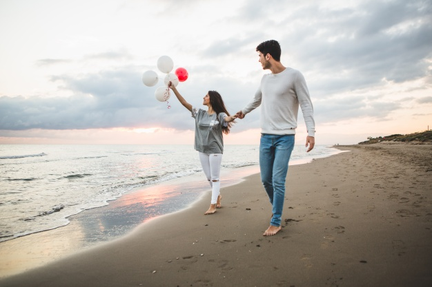 smiling-couple-walking-on-the-beach-with-balloons_23-2147595924