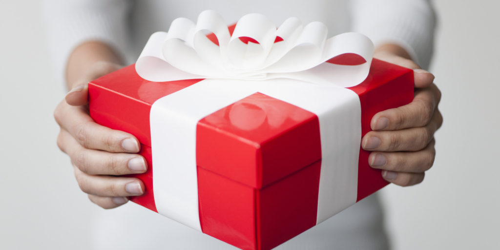 Woman holding gift box, cropped